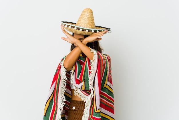 Jonge mexicaanse die vrouw op witte muur wordt geïsoleerd die twee gekruiste wapens houdt, ontkenningsconcept.