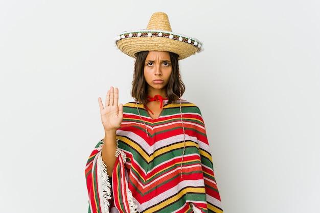 Jonge mexicaanse die vrouw op witte muur wordt geïsoleerd die zich met uitgestrekte hand bevindt die eindeteken toont, dat u verhindert.