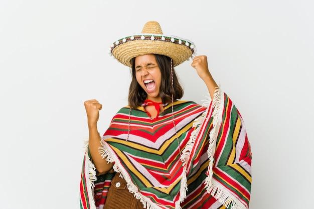 Jonge mexicaanse die vrouw op witte ruimte wordt geïsoleerd die vuist opheft na een overwinning, winnaarconcept.