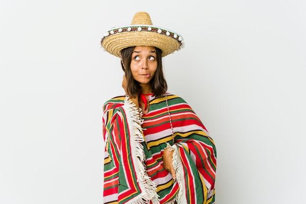 Jonge mexicaanse vrouw die achterkant van het hoofd raakt, denkt en een keuze maakt