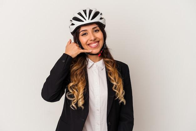 Jonge mexicaanse vrouw die een fiets berijdt om te werken dat op witte achtergrond wordt geïsoleerd die een mobiel telefoongesprekgebaar met vingers toont.