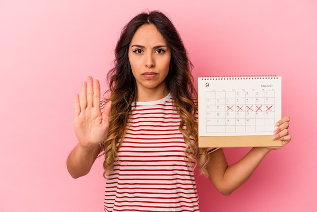 Jonge mexicaanse vrouw die een kalender houdt die op roze muur wordt geïsoleerd die zich met uitgestrekte hand bevindt die stopbord toont, dat u verhindert.