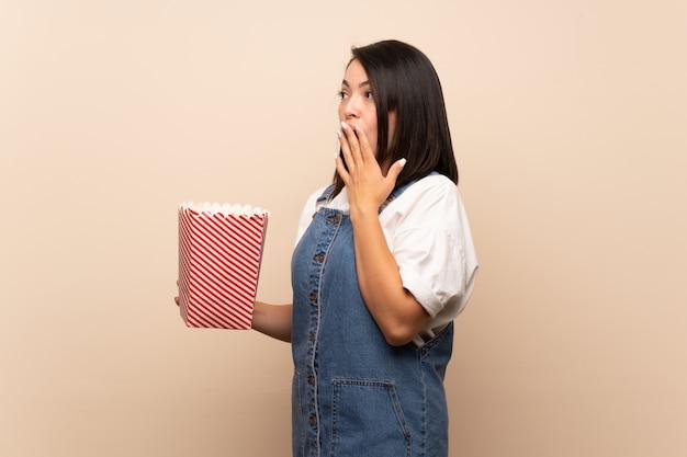 Jonge mexicaanse vrouw die een kom popcorns houdt
