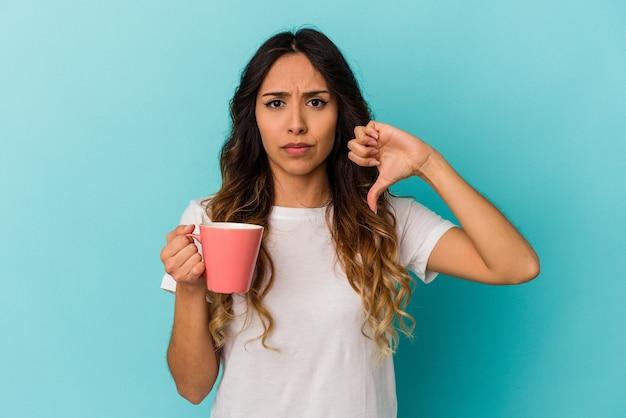 Jonge mexicaanse vrouw die een mok houdt die op blauwe achtergrond wordt geïsoleerd die een afkeergebaar, duimen naar beneden toont. meningsverschil concept.