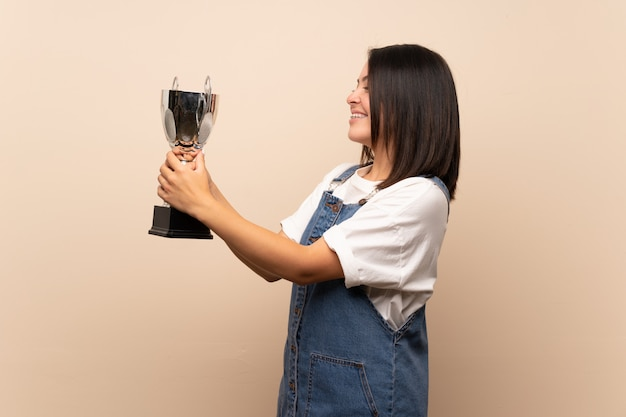 Jonge mexicaanse vrouw die een trofee houdt
