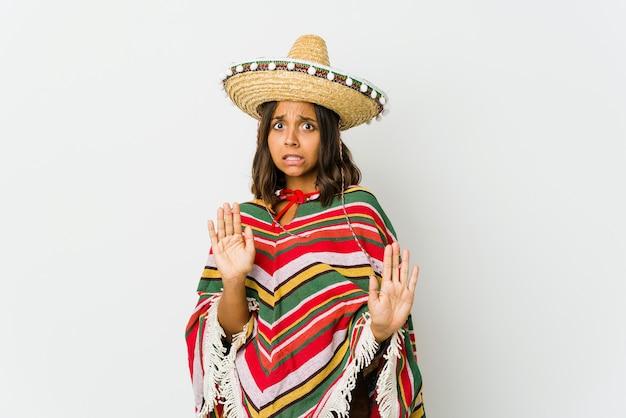 Jonge mexicaanse vrouw die iemand afwijst die een gebaar van walging toont.
