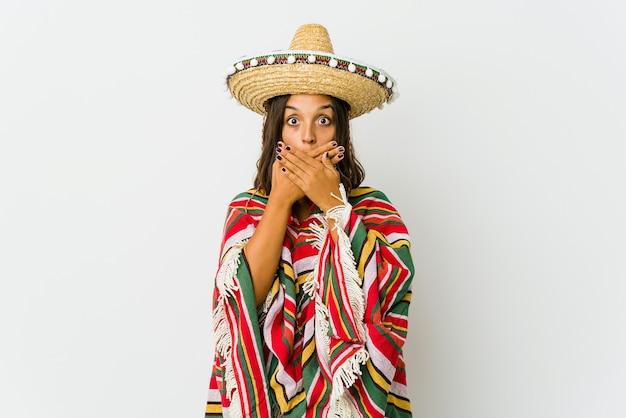 Jonge mexicaanse vrouw die mond met handen behandelt.