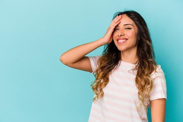 Jonge mexicaanse vrouw die op blauwe achtergrond wordt geïsoleerd die gelukkige, zorgeloze, natuurlijke emotie lacht.