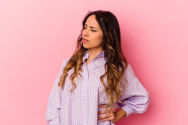 Jonge mexicaanse vrouw die op roze achtergrond wordt geïsoleerd die aan rugpijn lijdt.