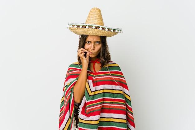 Jonge mexicaanse vrouw die op wit met vingers op lippen wordt geïsoleerd die een geheim houden.