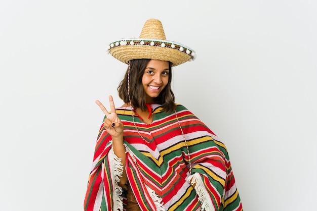 Jonge mexicaanse vrouw die op wit wordt geïsoleerd dat overwinningsteken toont en breed glimlacht.