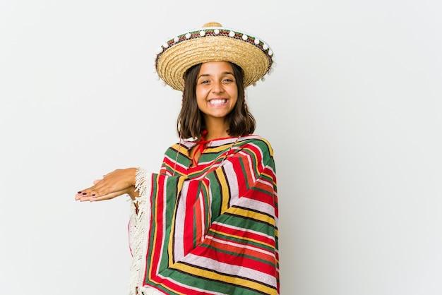 Jonge mexicaanse vrouw die op witte muur wordt geïsoleerd die een exemplaarruimte op een palm houdt.