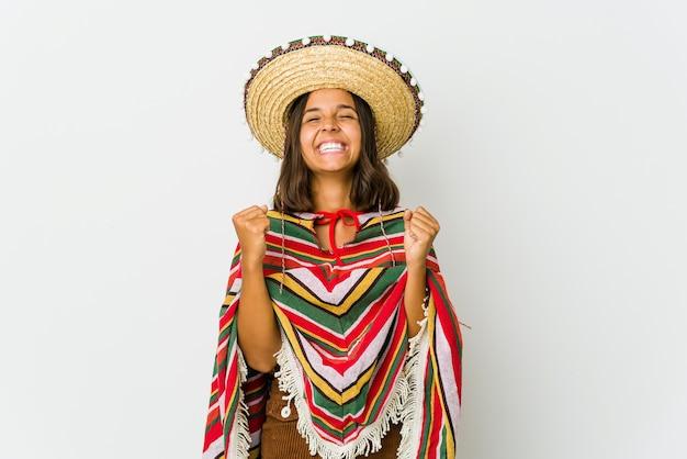 Jonge mexicaanse vrouw die op witte muur wordt geïsoleerd die een overwinning, hartstocht en enthousiasme, gelukkige uitdrukking viert.