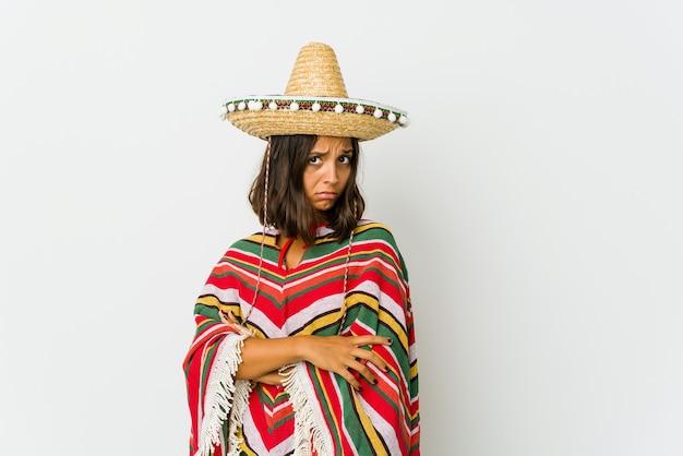 Jonge mexicaanse vrouw die op witte muur wordt geïsoleerd die verdacht, onzeker, u onderzoekt.