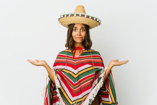 Jonge mexicaanse vrouw die op witte muur wordt geïsoleerd die verward en twijfelachtig schouders ophaalt om een exemplaarruimte vast te houden