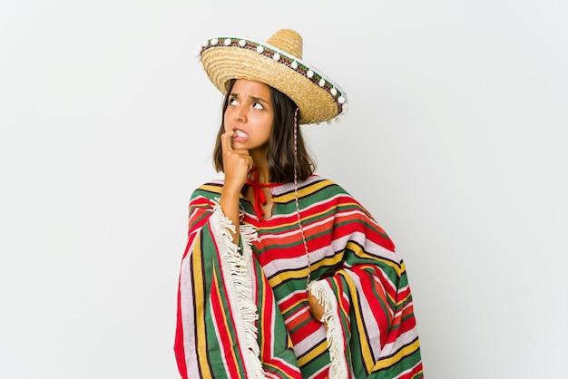 Jonge mexicaanse vrouw die opzij kijkt met een twijfelachtige en sceptische uitdrukking.