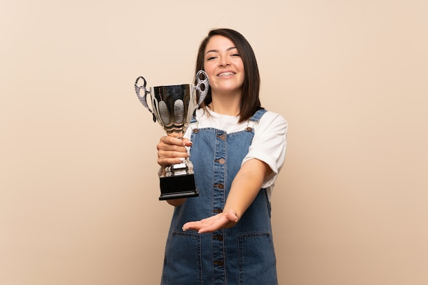 Jonge mexicaanse vrouw die over geïsoleerde muur een trofee houdt