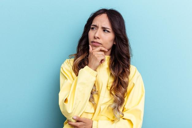 Jonge mexicaanse vrouw geïsoleerd op blauwe achtergrond denken en opzoeken, reflecterend zijn, nadenken, een fantasie hebben.