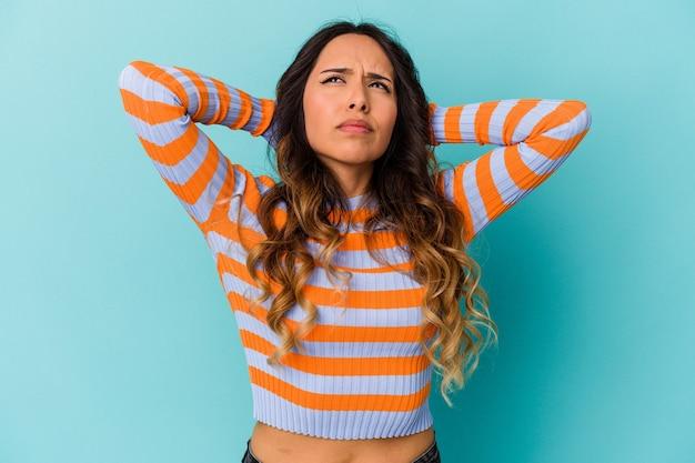 Jonge mexicaanse vrouw geïsoleerd op blauwe achtergrond nekpijn lijden als gevolg van een zittende levensstijl.