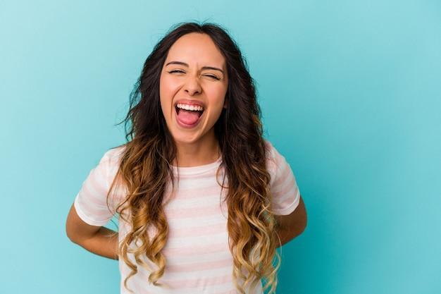 Jonge mexicaanse vrouw geïsoleerd op een blauwe achtergrond grappige en vriendelijke tong uitsteekt.