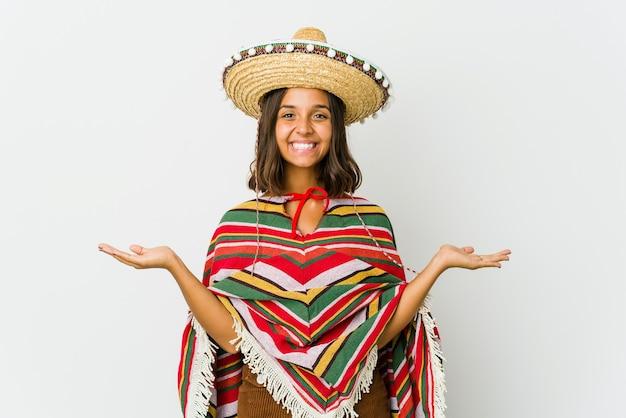 Jonge mexicaanse vrouw geïsoleerd op een witte achtergrond maakt schaal met armen, voelt zich gelukkig en zelfverzekerd.