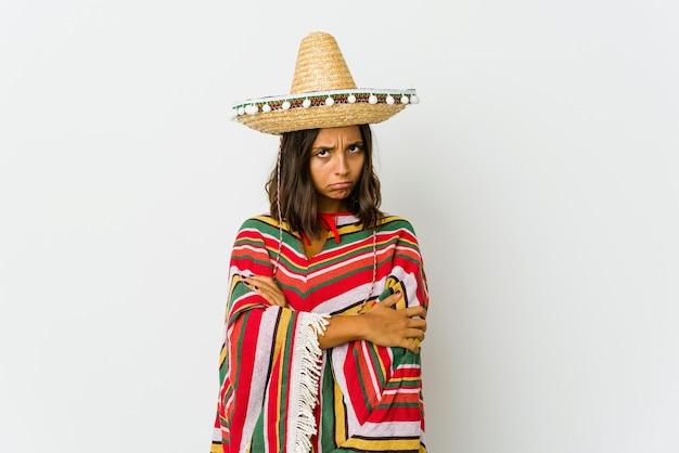 Jonge mexicaanse vrouw geïsoleerd op een witte muur fronsend gezicht in ongenoegen, houdt armen gevouwen
