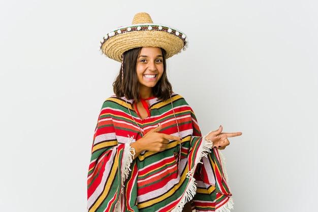 Jonge mexicaanse vrouw geïsoleerd op een witte muur opgewonden wijzend met wijsvingers weg.