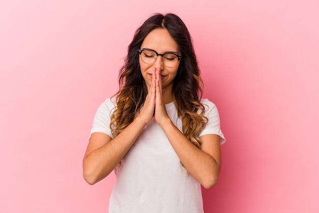 Jonge mexicaanse vrouw geïsoleerd op roze achtergrond hand in hand in bidden in de buurt van mond, voelt zich zelfverzekerd.