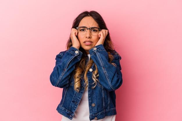Jonge mexicaanse vrouw geïsoleerd op roze achtergrond huilen, ongelukkig met iets, pijn en verwarring concept.