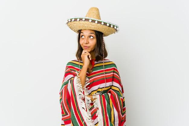Jonge mexicaanse vrouw geïsoleerd op wit ontspannen denken aan iets kijken naar een kopie ruimte.