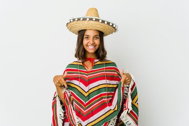 Jonge mexicaanse vrouw geïsoleerd op witte muur wijst naar beneden met vingers, positief gevoel.