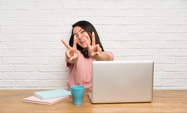 Jonge mexicaanse vrouw met laptop die en overwinningsteken glimlacht toont