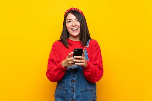 Jonge mexicaanse vrouw met overall over gele muur die een bericht met mobiel verzendt
