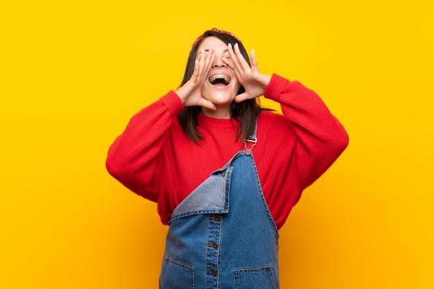 Jonge mexicaanse vrouw met overall over gele muur die en iets schreeuwen aankondigen