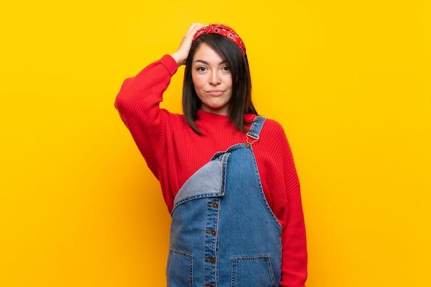 Jonge mexicaanse vrouw met overall over gele muur met een uitdrukking van frustratie