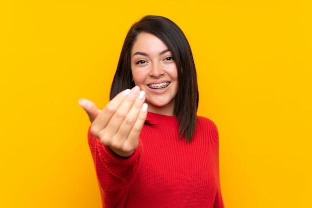 Jonge mexicaanse vrouw met rode sweater over gele muur die uitnodigt te komen
