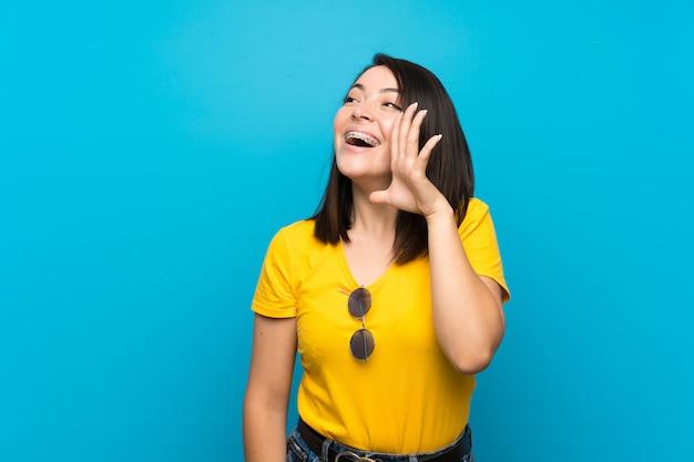 Jonge mexicaanse vrouw over geïsoleerd blauw schreeuwen met wijd open mond