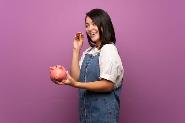 Jonge mexicaanse vrouw over geïsoleerd houdend een grote spaarpot