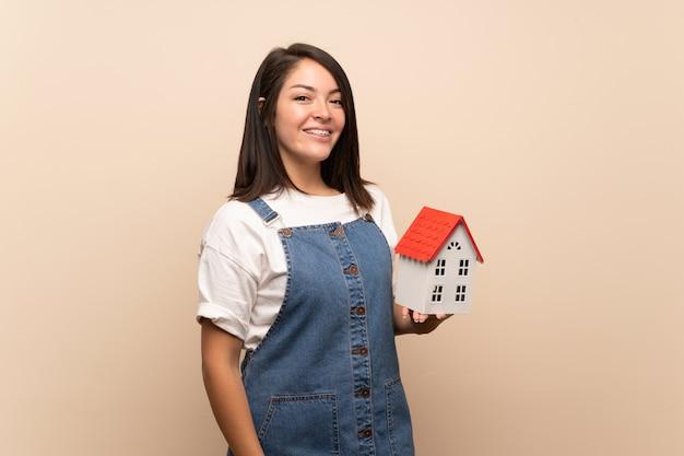 Jonge mexicaanse vrouw over geïsoleerd houdend een klein huis