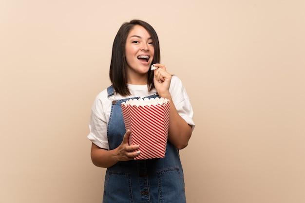 Jonge mexicaanse vrouw over geïsoleerd houdend een kom popcorns