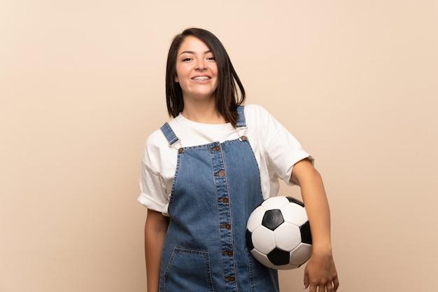 Jonge mexicaanse vrouw over geïsoleerd houdend een voetbalbal