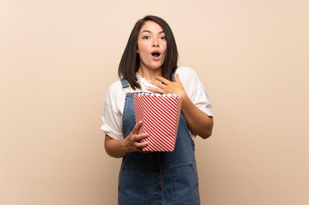 Jonge mexicaanse vrouw over geïsoleerde achtergrond die een kom popcorns houdt
