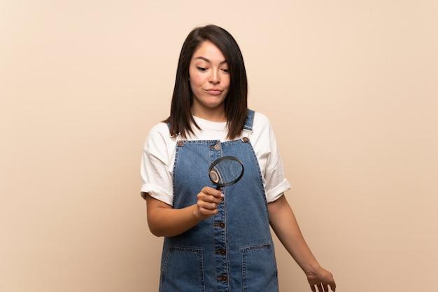 Jonge mexicaanse vrouw over geïsoleerde achtergrond die een vergrootglas houdt