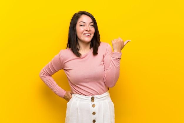 Jonge mexicaanse vrouw over geïsoleerde gele achtergrond die aan de kant richt om een product te voorstellen