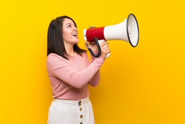 Jonge mexicaanse vrouw over geïsoleerde gele achtergrond die door een megafoon schreeuwt