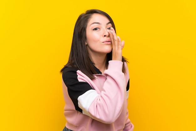 Jonge mexicaanse vrouw over geïsoleerde gele achtergrond die iets fluistert