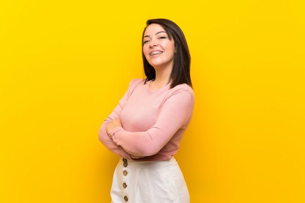 Jonge mexicaanse vrouw over geïsoleerde gele achtergrond met gekruiste en wapens die vooruit eruit zien