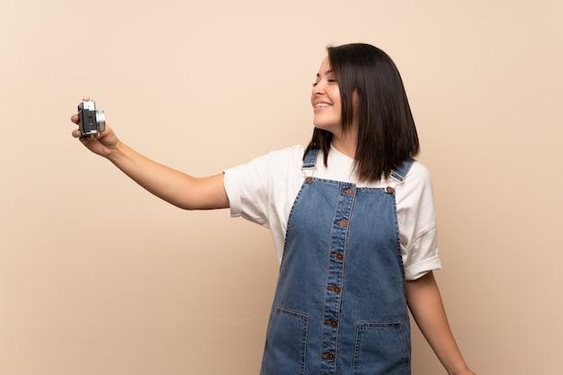 Jonge mexicaanse vrouw over geïsoleerde het maken van een selfie