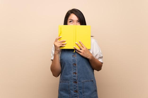 Jonge mexicaanse vrouw over geïsoleerde holding en het lezen van een boek