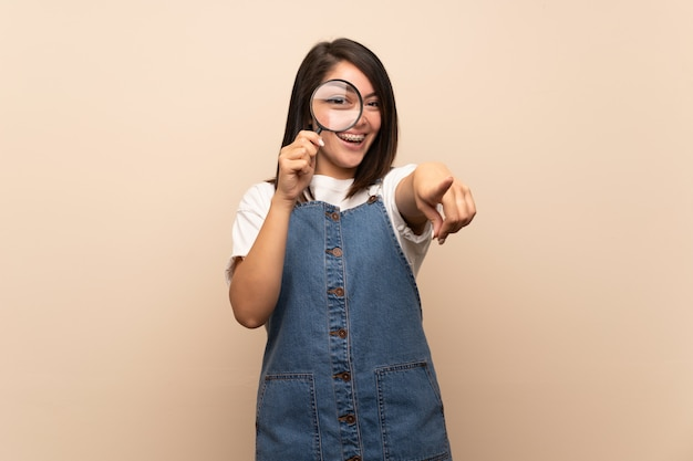 Jonge mexicaanse vrouw over geïsoleerdee holding een vergrootglas